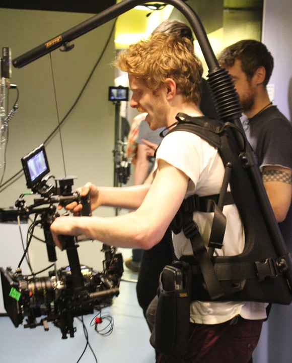 a man wearing a lot of camera equipment on set