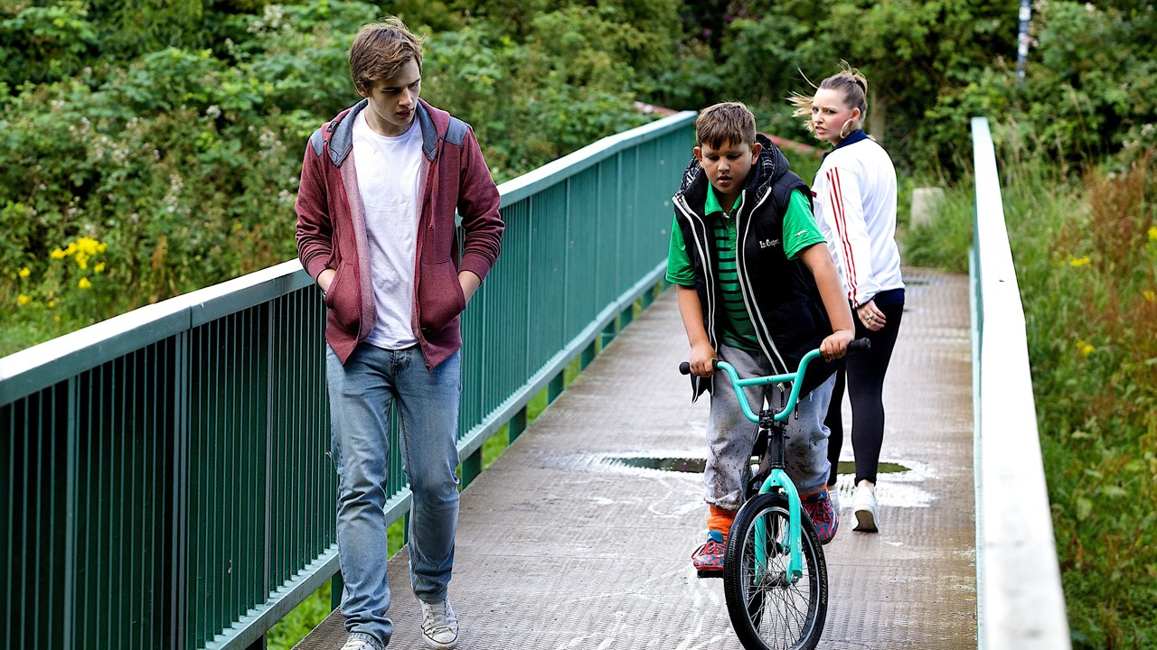 two boys, one cycling over a bridge