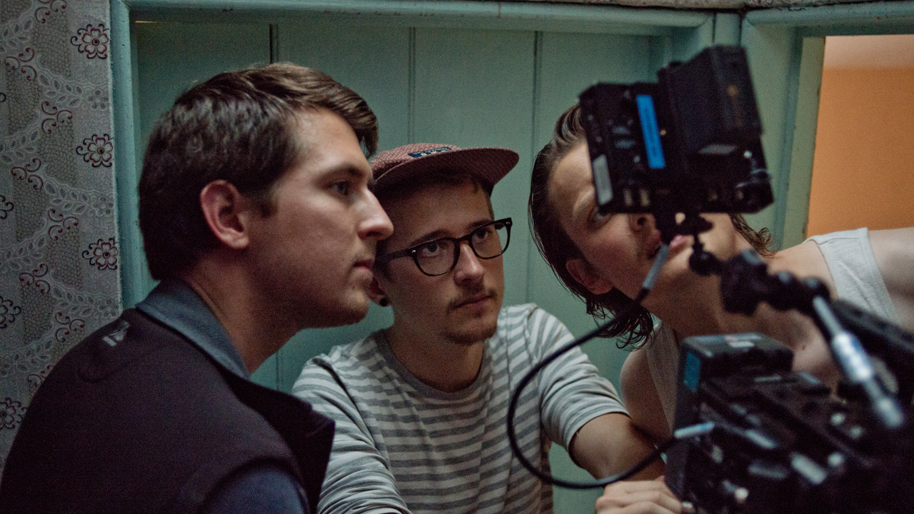 three men crowding round a camera and small monitor on set
