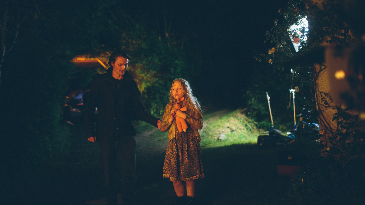 a man and girl at night being filmed outside
