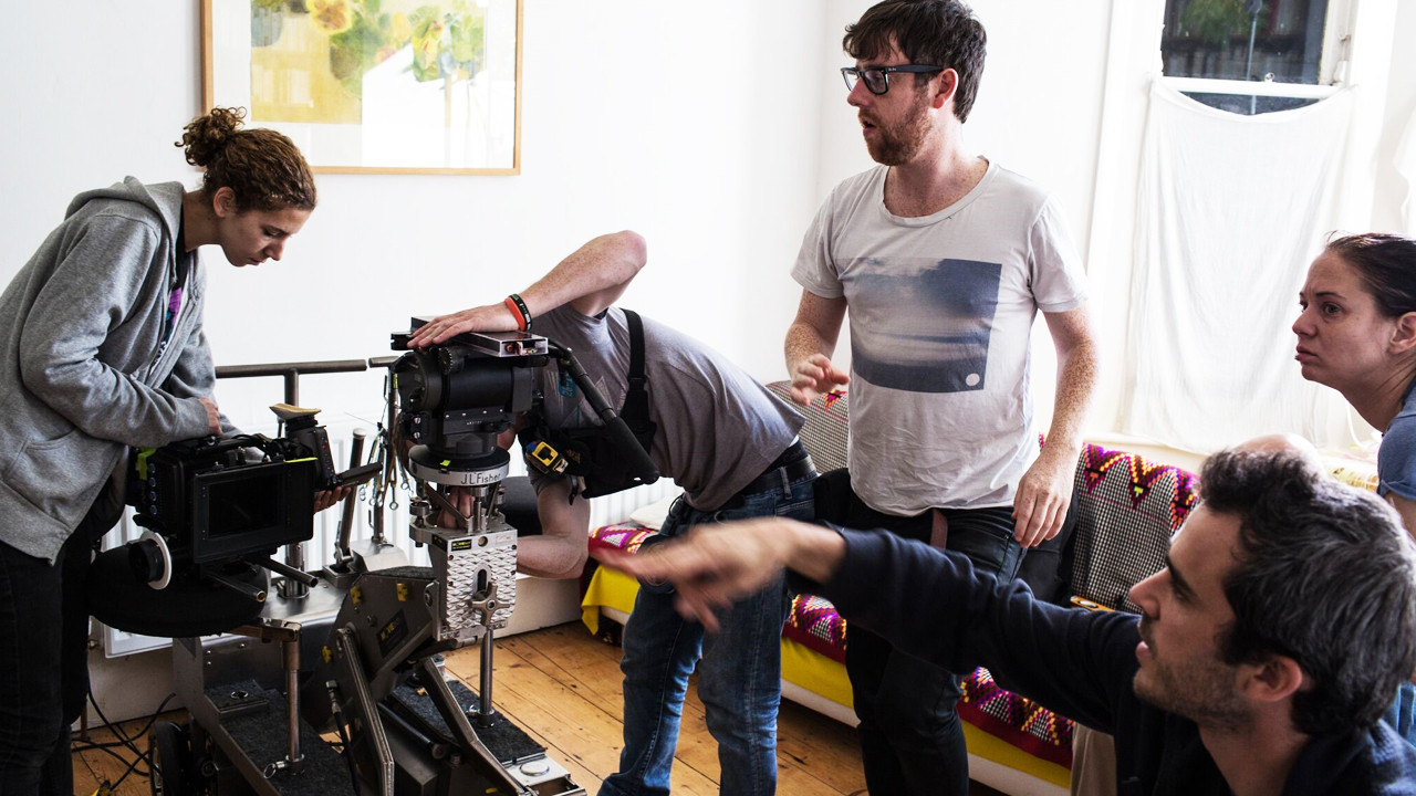 a group of people with large camera equipment in a house