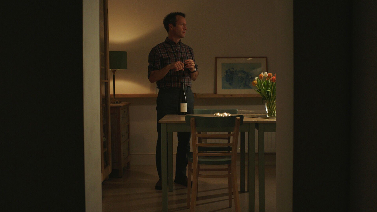 a man stands in his kitchen with a bottle of wine on the table