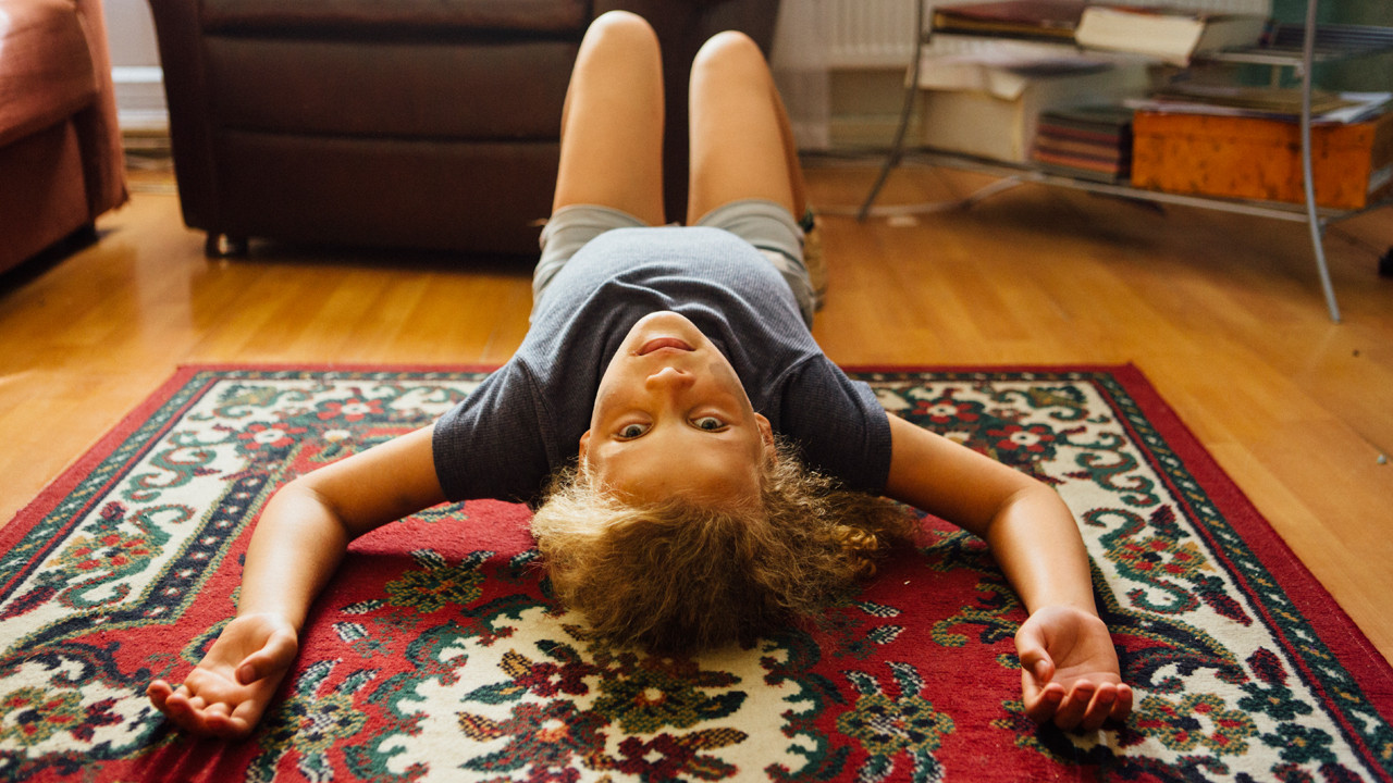 a girl lying on her back on a rug
