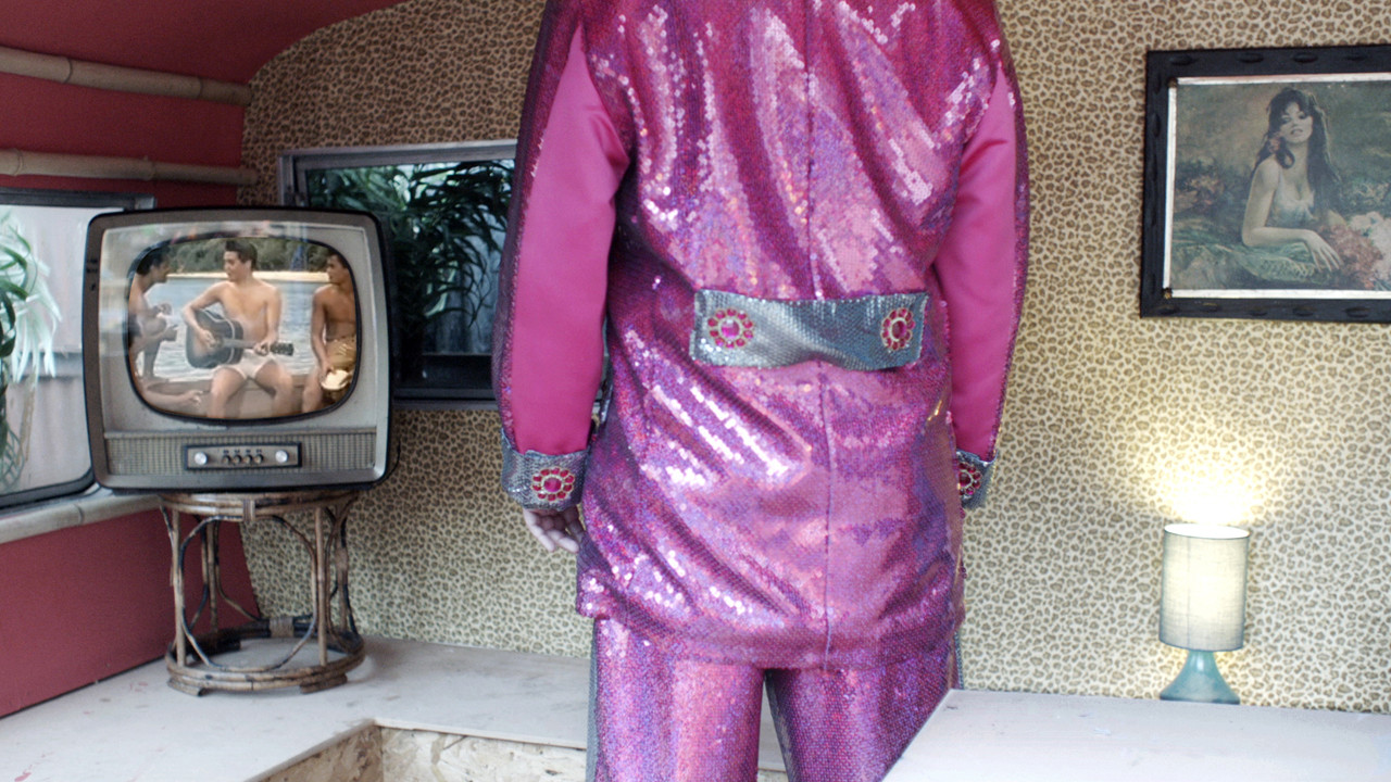 the back of a man in a pink sequin outfit watching a television set