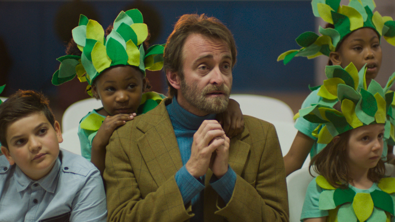 a man holding his hands together with children in leaf costumes around him