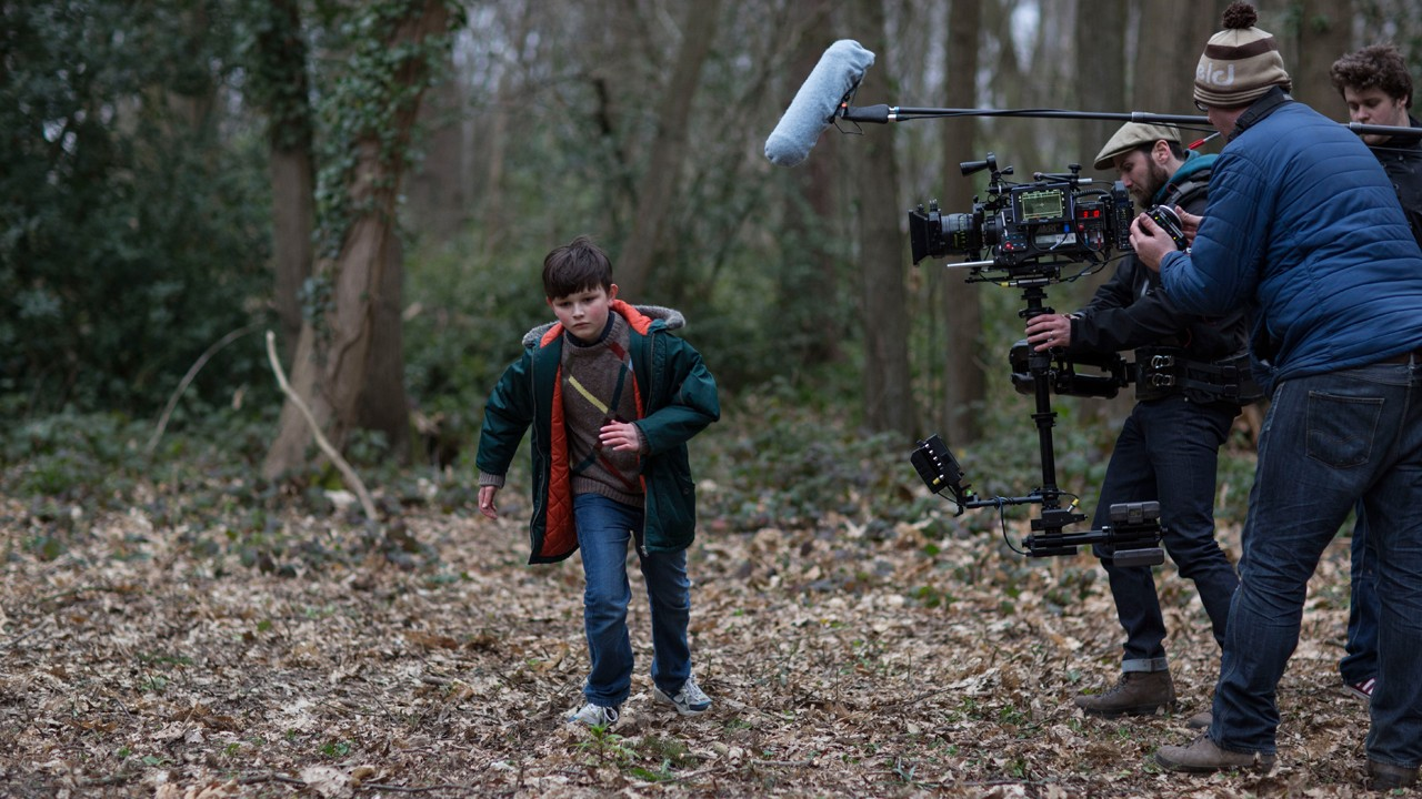 on set in wood filming small boy