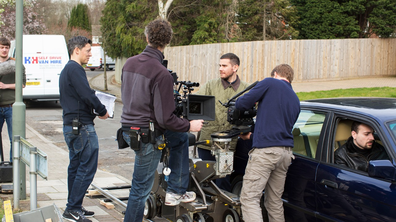 4 men on set in the street with filming equipment