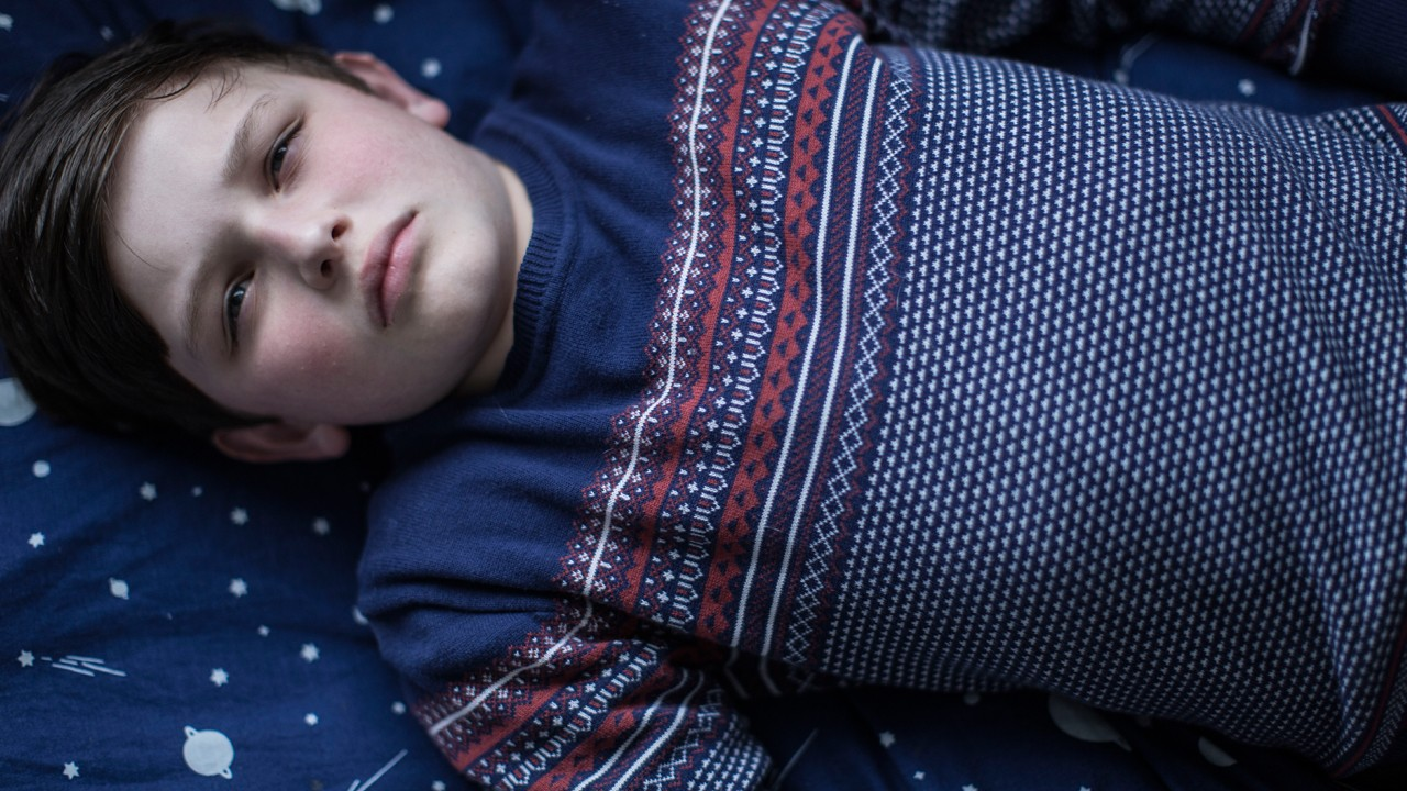 a little boy in a Christmas jumper lying down