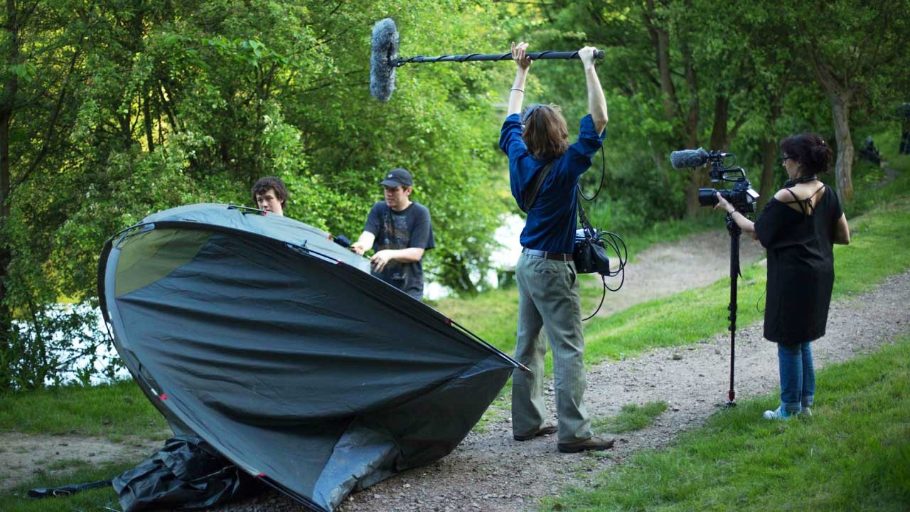 The crew are filming around a tent by the lake