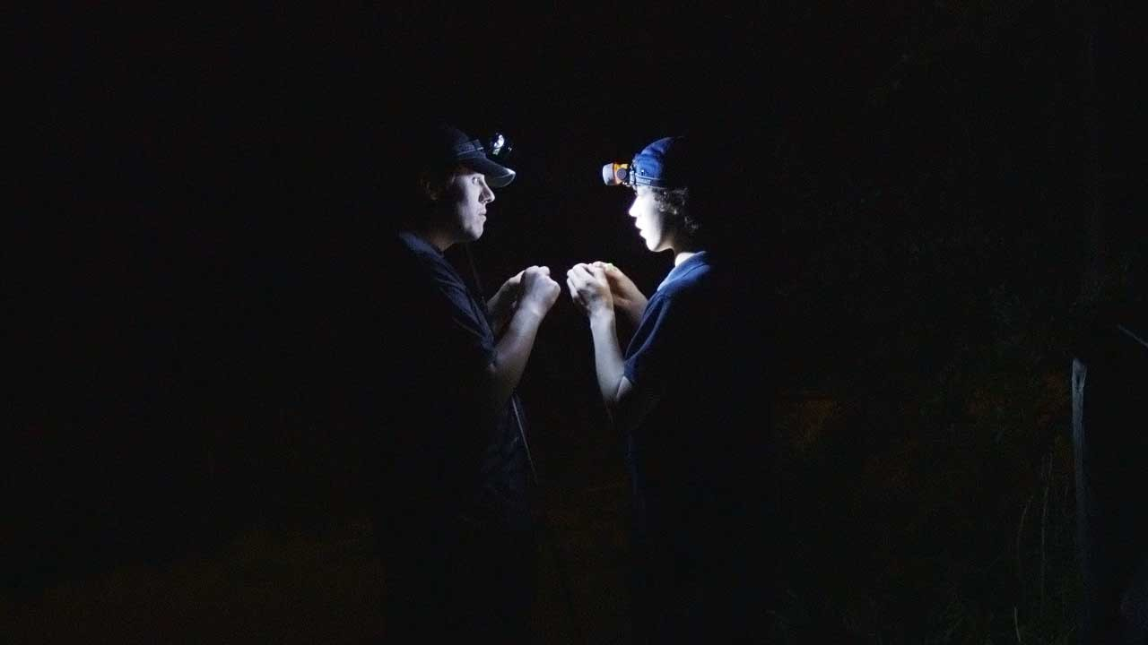two boys are setting their fishing rods in the dark