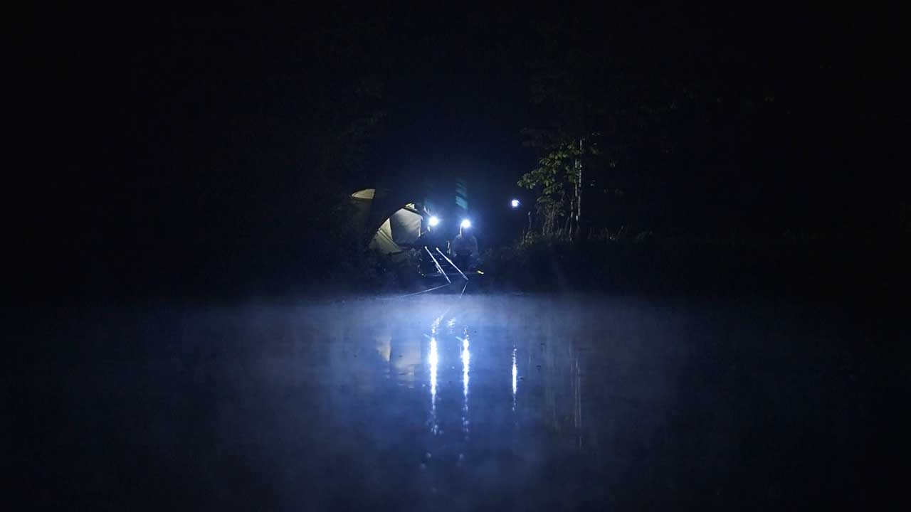 two boys sit across a lake at night