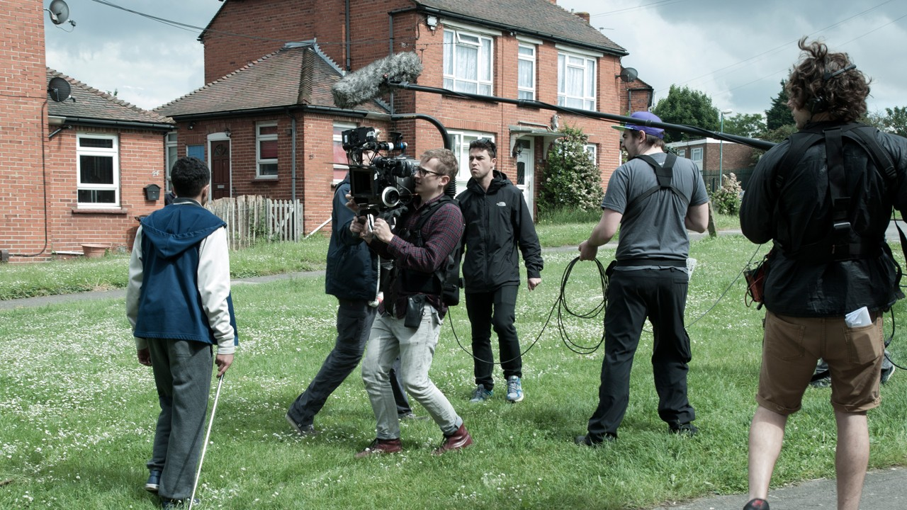 the crew filming on set outside front of the house