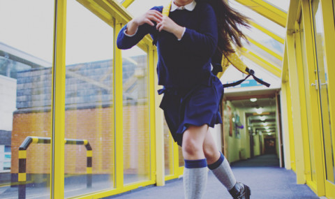 a girl running down a school corridor