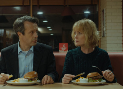 a man and a woman sit a table at a diner